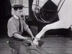 A new customer tries on a shoe for size in The Blacksmith (1922), a comedy short starring Buster Keaton
