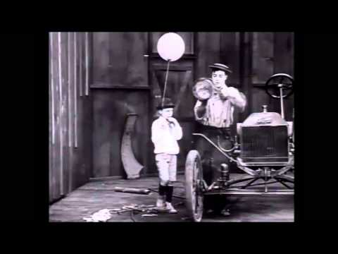 A kid with a balloon antagonizes Buster Keaton in The Blacksmith (1922)