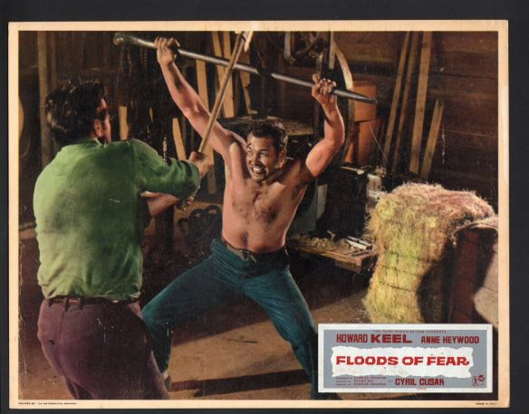 Howard Keel as an escaped prisoner (who was falsely incarcerated) defends himself in Floods of Fear (1958).