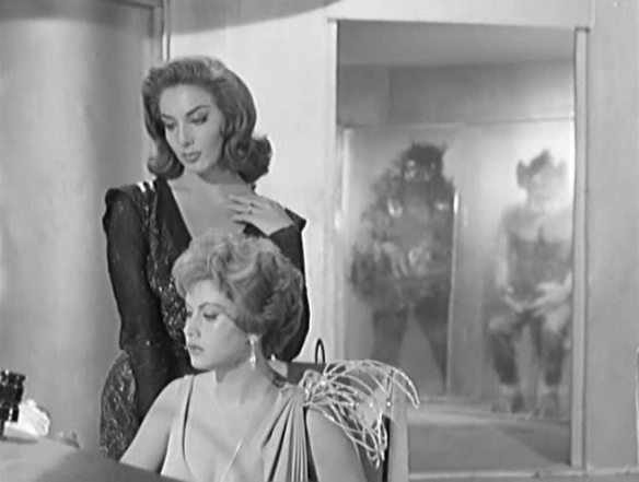Beta (Lorena Veláquez, left) and Gamma (Ana Bertha Lepe) man their spaceship while various alien specimens hover in the background in The Ship of Monsters (1960)