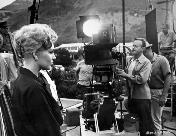 Kim Novak on the set of Strangers When We Meet (1960), with director Richard Quine in the background adjusting her lighting