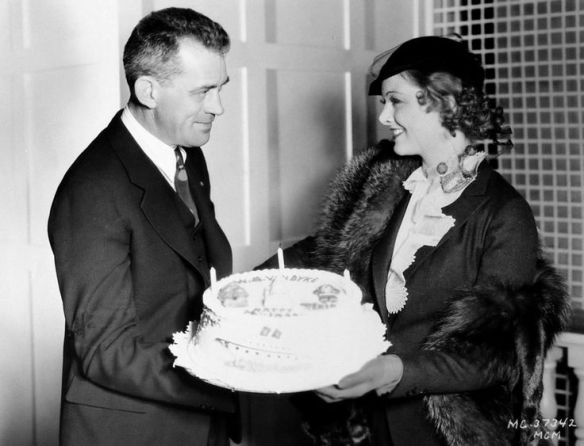 Director W.S. Van Dyke presents Myrna Loy with a birthday cake on the set of Manhattan Melodrama (1934).